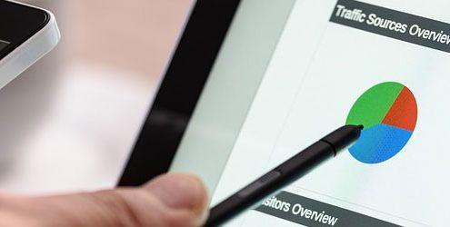 Mano che tiene una penna e indica grafici sullo schermo di un notebook