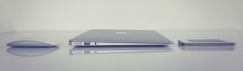 Apple Magic Mouse, Apple Macbook e Apple iPhone appoggiati su piano grigio