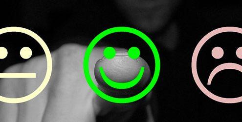 Customer Care: Uomo che indica uno smile sorridente in primo piano di colore verde accompaganto da altri due smile