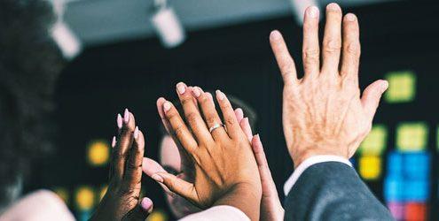 Mani di uomini e donne d'affari che esultano