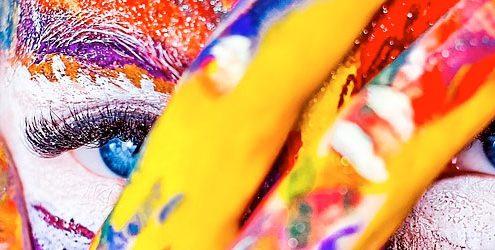 Viso di donna con mano in primo piano pitturata di vari colori