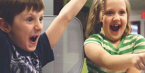 Bambino e bambina che esultano di fronte allo schermo di un pc