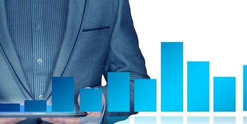 Uomo d'affari o Business Man vestito di blu su sfondo bianco e grafico a barre in primo piano