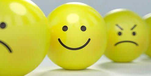 Sentiment Analysis: Palle di gomma gialle che rappresentano vari smiley su tavolo bianco