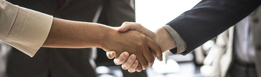 Stretta di mano tra uomo e donna in ambiente lavorativo