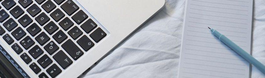 Immagine di Macbook e taccuino con penna su un telo bianco