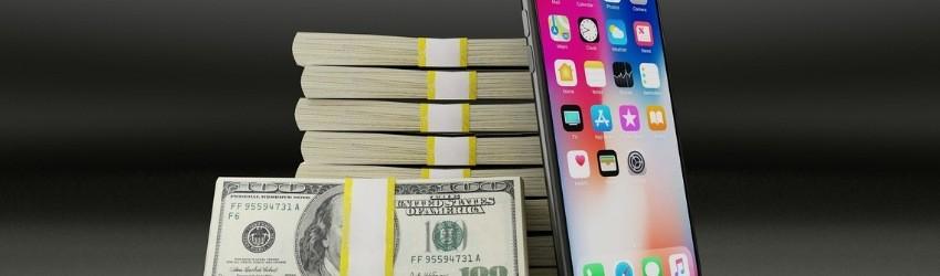 pila di banconote rilegate con una fascetta a cui sono appoggiati una fascetta di 100 dollari e un I-Phone acceso su sfondo grigio scuro