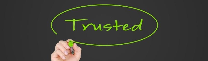 """Mano che scrive con pennarello verde """"Trusted """"cerchiato su sfondo grigio scuro"""