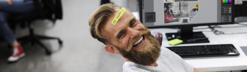 "Uomo sorridente davanti a un computer con post-it giallo in fronte con scritto ""be happy"" con"