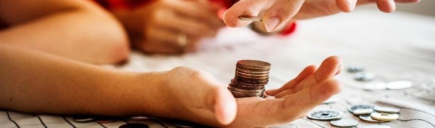 mano tesa che regge monete impilate con sopra un altro mano che aggiunge monete sopra un tavolo con altre monete poggiate