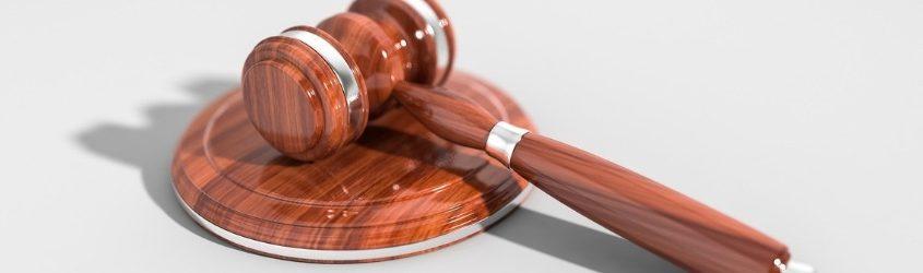 sanzioni: martelletto del giudice in legno lucido su sfondo bianco