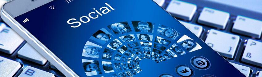 smartphone con schermata Social con sotto foto di utenti, poggiato sulla tastiera di un computer, tutto sui toni del blu