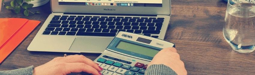 Mani di donna con calcolatrice davanti a un pc poggiato su un tavolo con bicchiere e cartella arancione