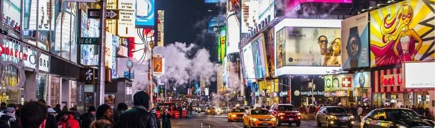 Strada affollata di una grande città con macchine e pareti dei grattacieli coperte di schermi che passano pubblicità
