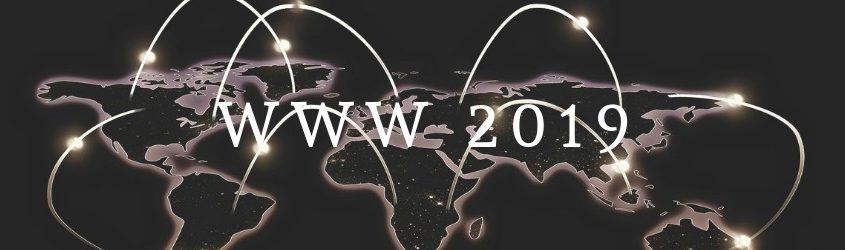 """scritta """"WWW 2019"""" su sfondo di una mappa del mondo scura con continenti evidenziati e fasci di luce che li connettono"""