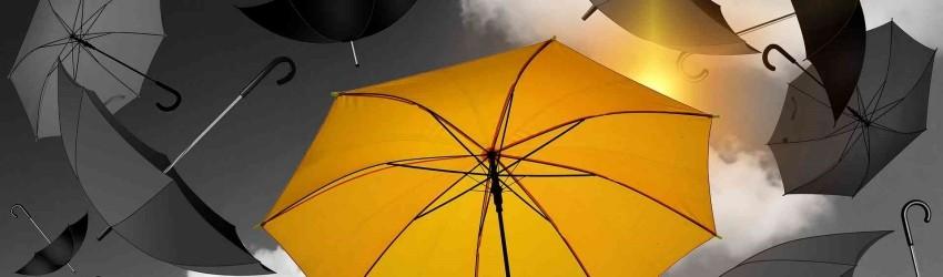 Ombrello giallo su sfondo di cielo e ombrelli in bianco e nero