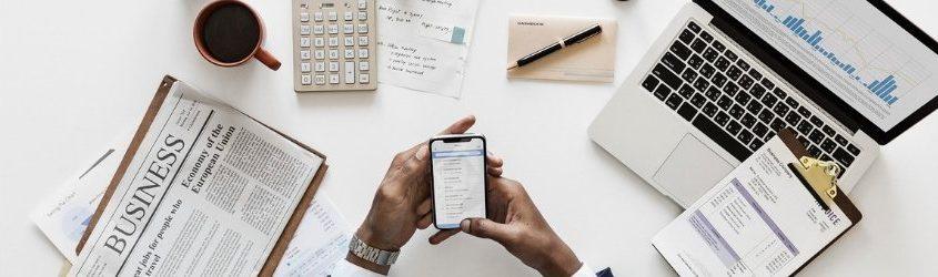 Business 2019: mani di uomo che reggono uno smartphone sopra ad un tavolo bianco sui cui poggiano un giornale finanziario, uno smartphone, una calcolatrice, vari documenti, un libretto degli assegni, una tazza e una piantina grassa