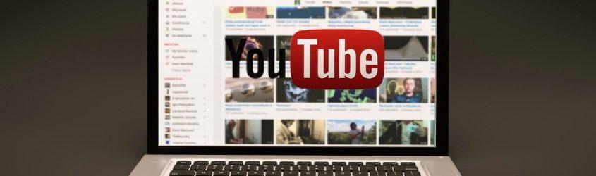 Canale YouTube Aziendale: laptop aperto su una pagina di YouTube con logo della piattaforma in sovraimpressione su sfondo grigio