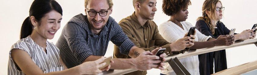 Social Media Trends 2019: due ragazzi e tre ragazze appoggiati ad una balaustra che guardano il proprio smartphone e interagiscono fra di loro