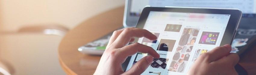 Insight consumatori 2018: donna che sta scorrendo una pagina di e-commerce su un tablet su sfondo di un tavolo con sopra un computer aperto sulla pagina dell'e-mail personale