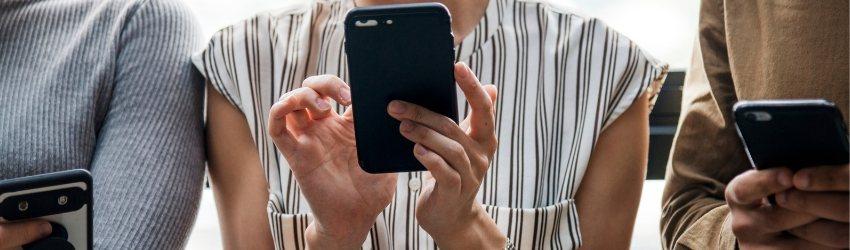 Insight consumatori 2018: zoom su tre persone che utilizzano lo smartphone che hanno fra le mani