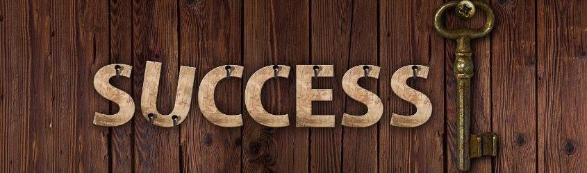 """chiave della Vendita: pannello di legno con appese lettere in legno che formano la scritta """"success"""" con accanto appesa una chiave antica"""
