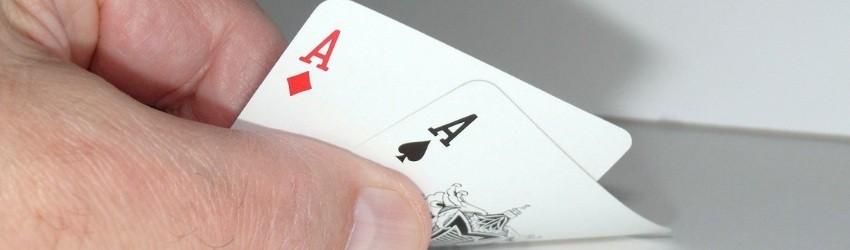 chiave della Vendita: mano di uomo che mostra due assi sollevando leggermente le carte da gioco dal tavolo