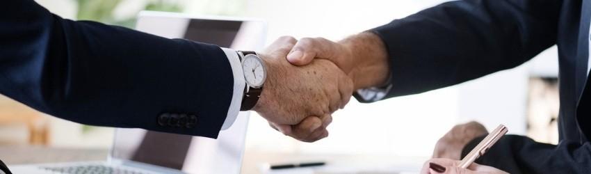 chiave della Vendita: stretta di mano tra due uomini d'affari sopra una scrivania