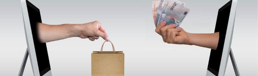 e:commerce: due pc uno di fronte all'altro da cui sbucano due braccia di uomo, una che porge una busta e una che dà delle banconote euro