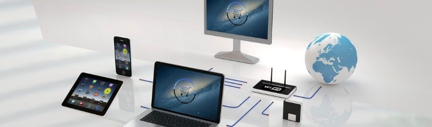 e-commerce: due schermi di computer che mostrano un carrello, collegati a un tablet, uno smartphone, a un router wi-fi e al mondo su sfondo bianco lucido