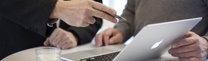 Cliente indeciso: uomo d'affari indica con una penna in mano lo schermo di un computer ad un altro uomo di fianco a lui che ascolta