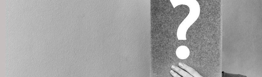 Cliente Indeciso: persona che tiene con una mano davanti alla faccia un cartello grigio con un punto di domanda bianco su sfondo grigio
