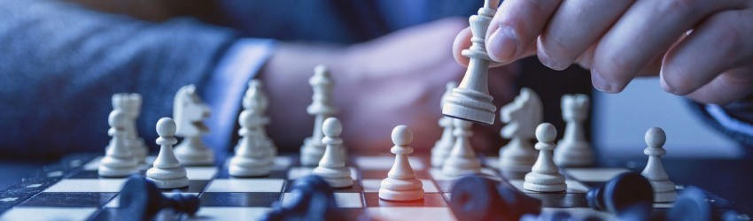 Pianificare al meglio la Strategia: uomo che muove una pedina bianca su una scacchiera