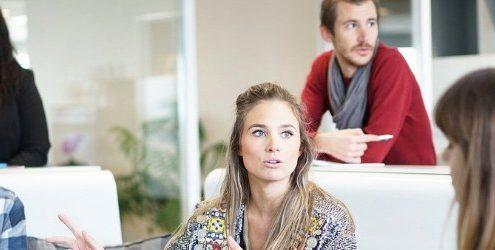 Pianificare la migliore Strategia: meeting aziendale informale con una donna al centro che parla e tre altre ragazze e un ragazzo la ascoltano e interagiscono fra di loro