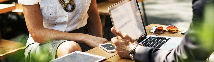 Consulente: uomo che consulta un pc su un tavolino con tablet e smartphone, di fronte a donna che lo ascolta