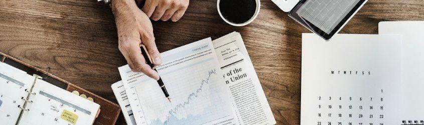 braccia di uomo vestito elegante con mano che con una penna indica una grafico rivolto verso il cliente su una scrivania con computer, tazza di caffè e fogli con statistiche di business