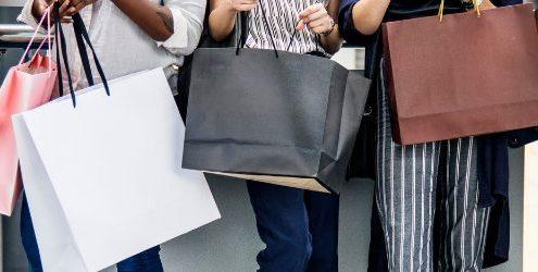 Consumatore: ragazzi e ragazza in fila con buste degli acquisti fra le mani