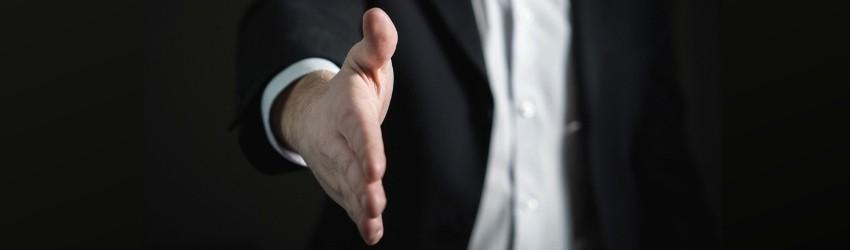 promuovere la tua azienda: uomo d'affari che tende la mano per una stretta di mano