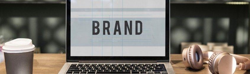 promuovere la tua azienda: schermo di laptop che mostra la parola brand, laptop poggiato su un tavolo con vicino una tazza usa e getta di caffè e un paio di cuffie