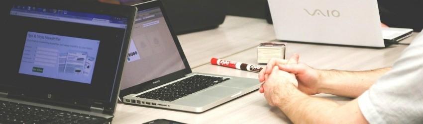Fondo Nazionale Innovazione: membri di una startup seduti ad un tavolo con i loro computer davanti che parlano di strategia aziendale