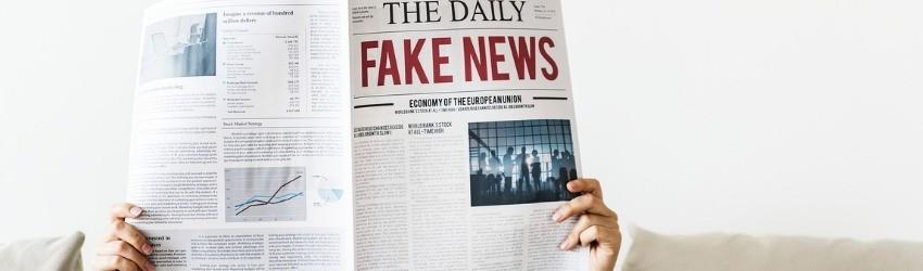 Fake News Elezioni Europee: donna che tiene un giornale aperto davanti al volto con scritto Fake News in prima pagina