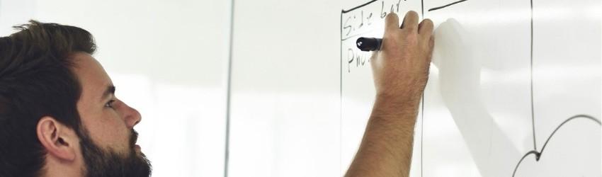 Errori vendita: Ragazzo che scrive con un pennarello nero su una lavagna bianca la strategia aziendale