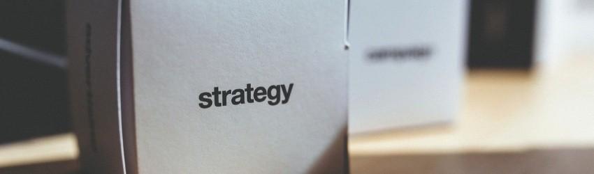 """Errori vendita: scatola bianca di carta con scritto """"strategia"""" sopra, poggiata su un tavolo con altre scatole uguali"""