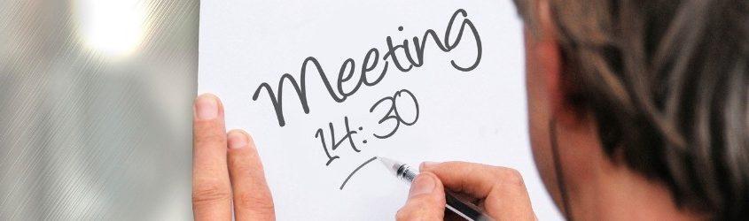 Controllo sulle Vendite: uomo d'affari che segna con una penna nera su un foglio appeso al muro un appuntamento