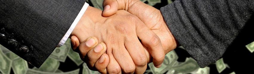 Controllo sulle Vendite: due uomini d'affari che si stringono la mano su sfondo nero con dollari volanti