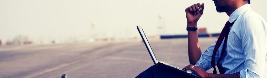 17 ipotesi per vendere di più: uomo d'affari seduto sull'asfalto con un computer poggiato sulle gambe che pensa