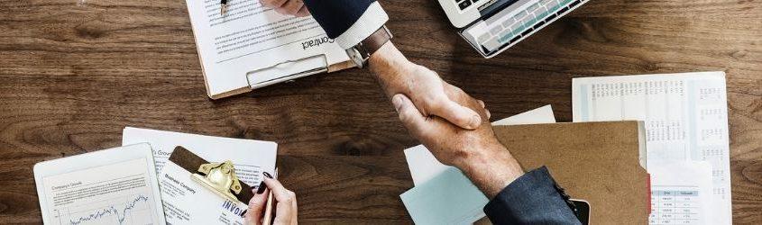 Vendere alle altre aziende: due uomini d'affari che si stringono la mano sopra una scrivania con una segretaria che prende appunti