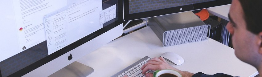Competenze digitali: uomo che lavora ad una scrivania con una tazza di caffè in mano che digita su una tastiera bluetooth e guarda uno dei due schermi di fronte a lui