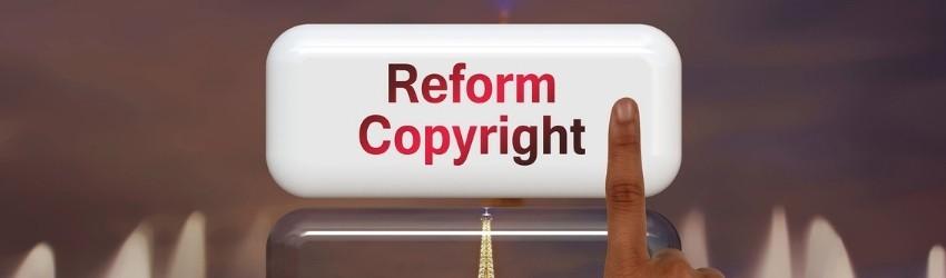 """Direttiva Europea Copyright: dito che clicca un pulsante con scritto """"reform copyright"""" in rosso"""