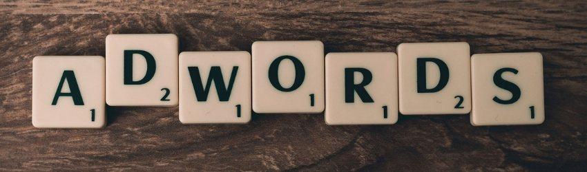 """Digital Marketing Punteggio Ottimizzazione: scritta """"adwords"""" formata da caselle dello scarabeo poggiate su un tavolo di legno"""